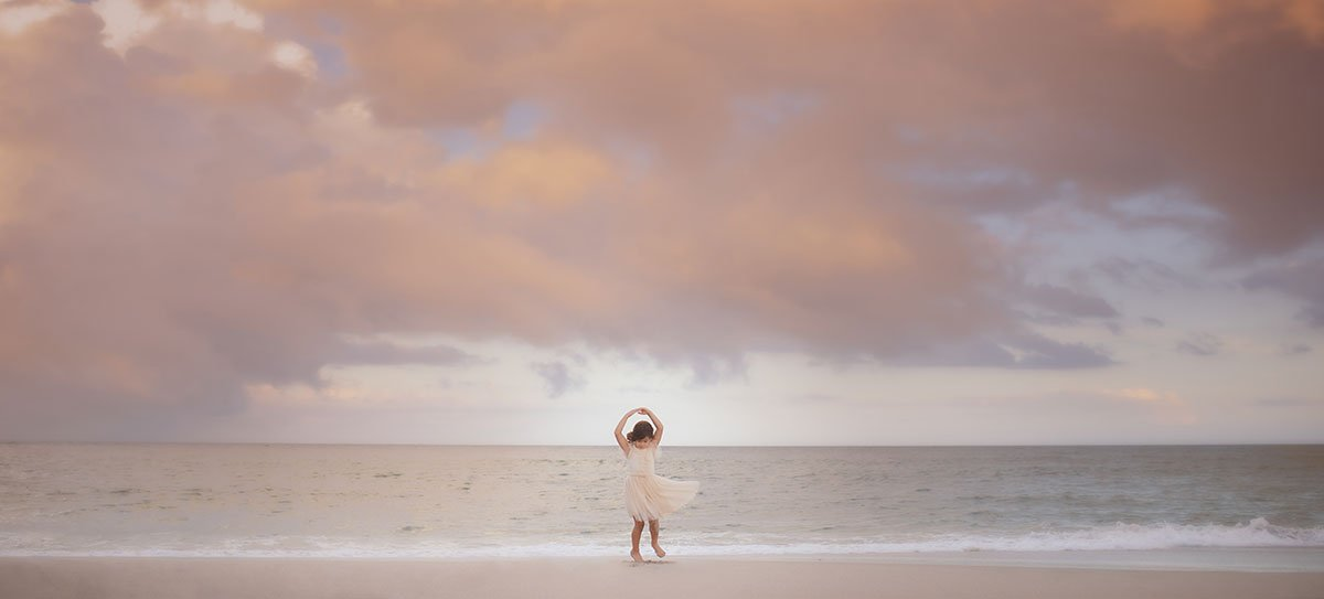 Girl in a tutu dancing on a beach
