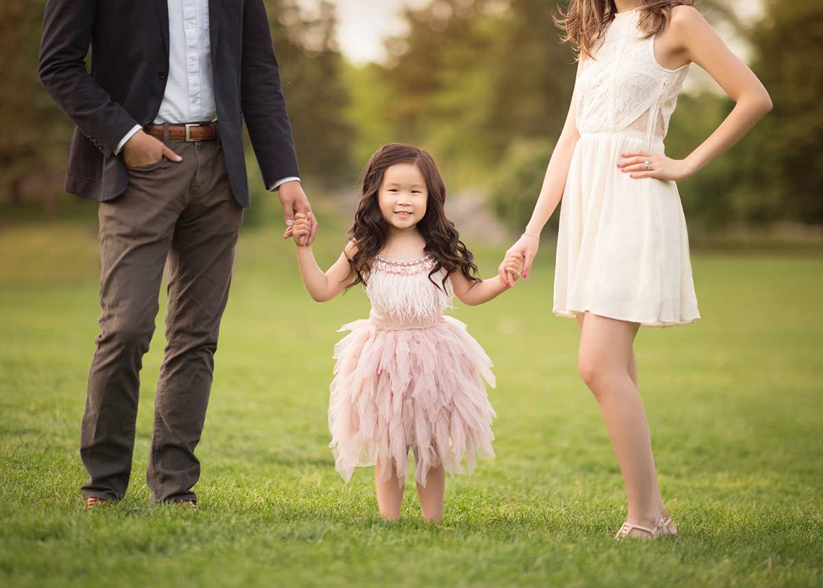 Girl wearing a tutu holding her parents' hands