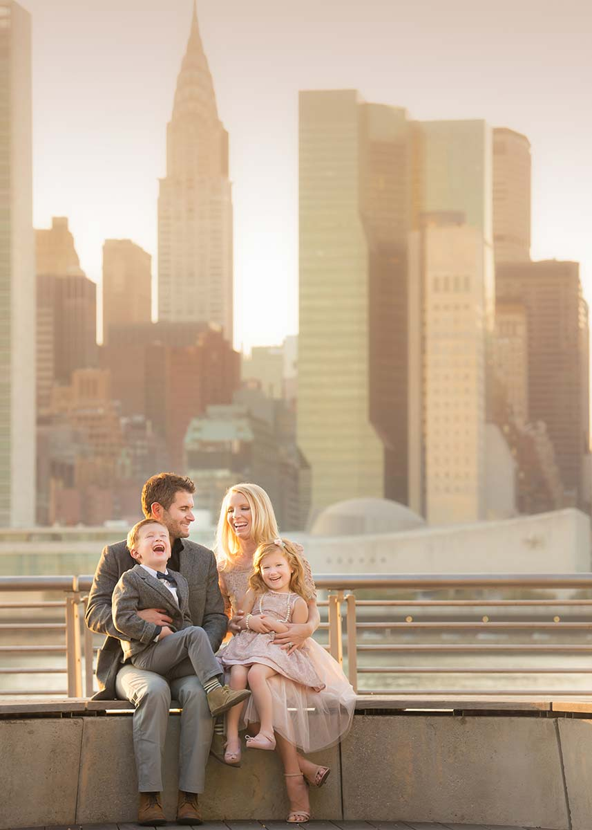 Modern family posing for a portrait near the NYC skyline