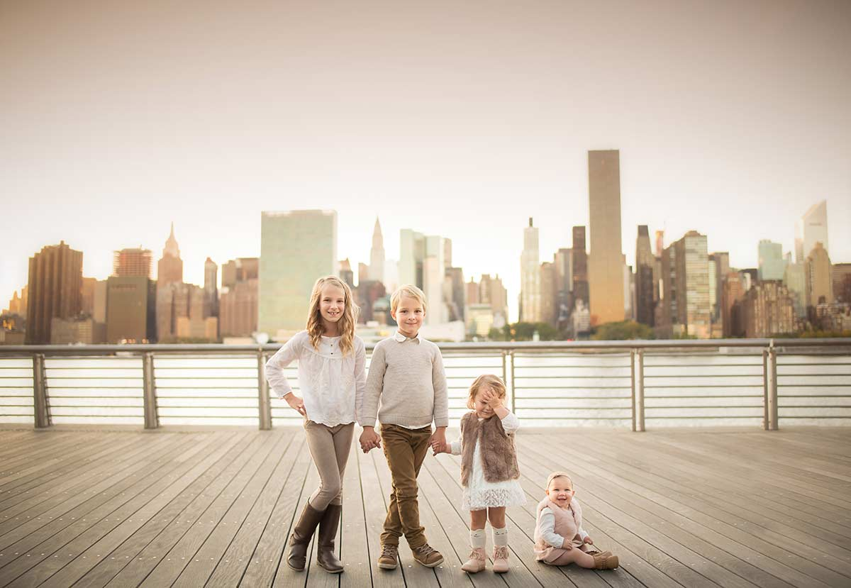 Four siblings posing for a portrait near NYC skyline