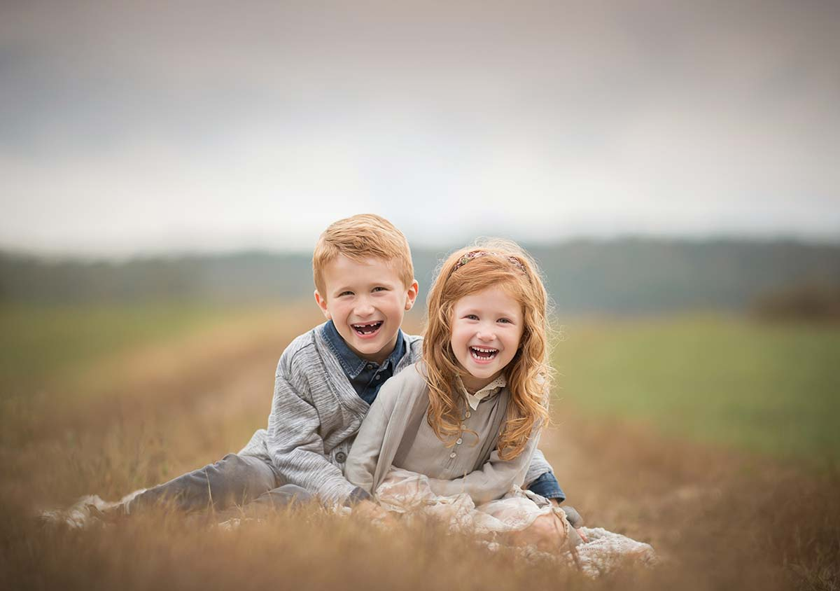 Brother and sister with red hair sitting and posing for a portrait