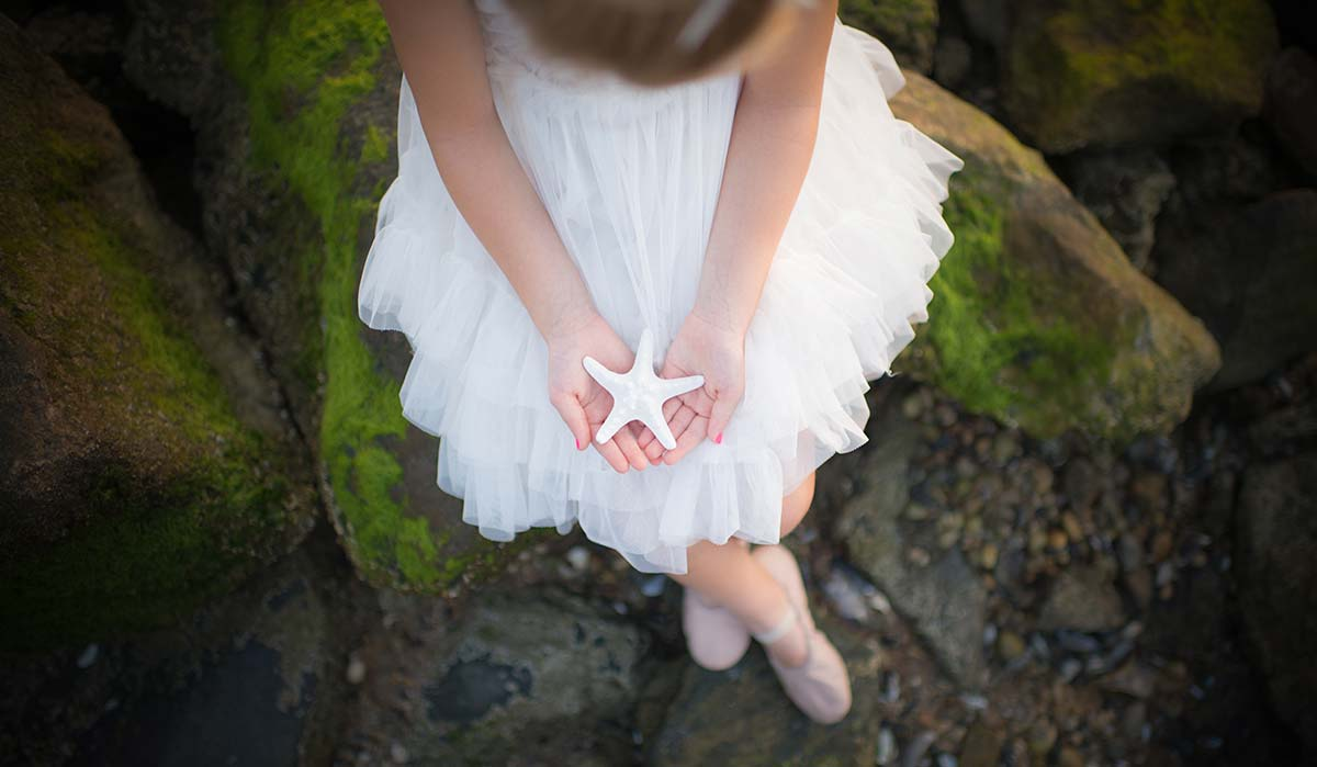 Girl in a tutu holding a starfish