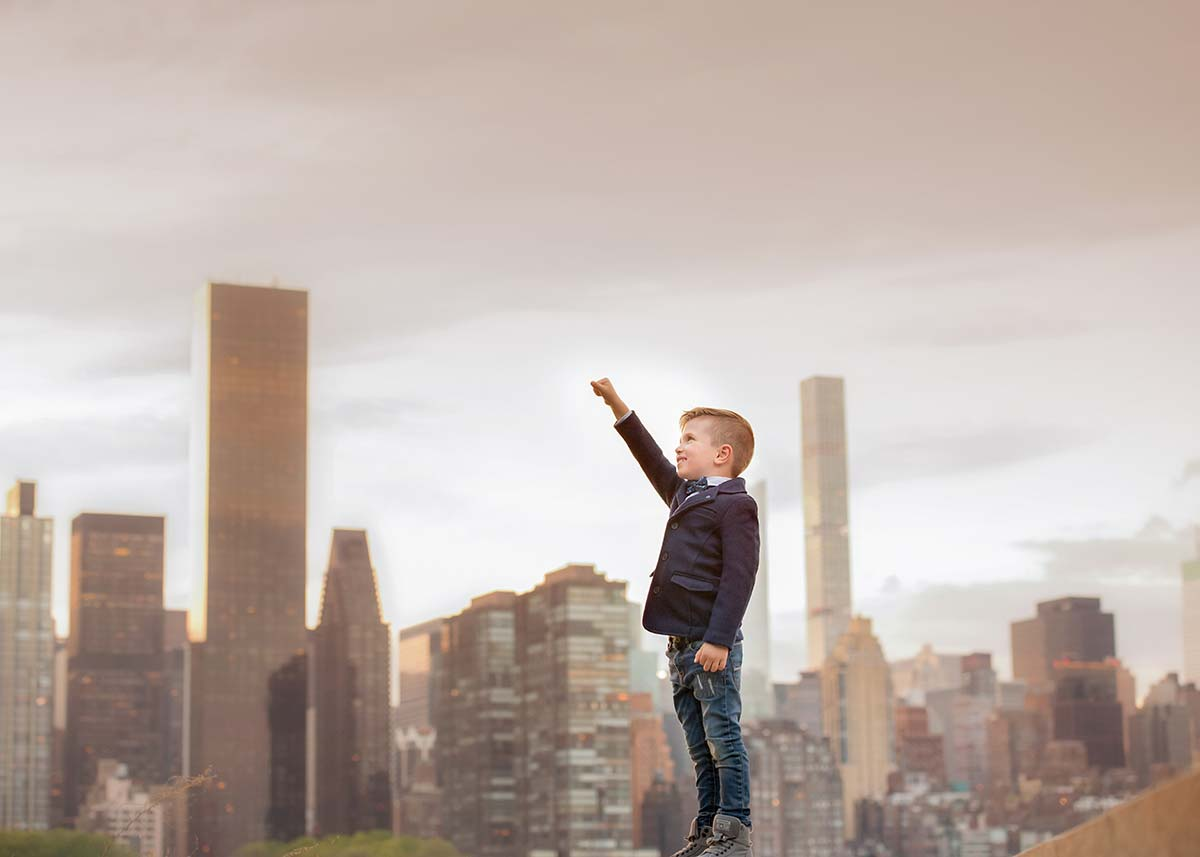 Stylish young boy holding his hand up with NYC skyline