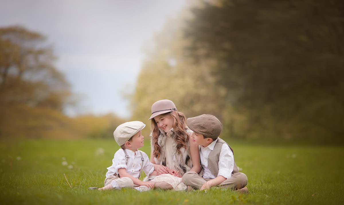 Three siblings dressed stylishly sitting in grass and sharing a happy moment
