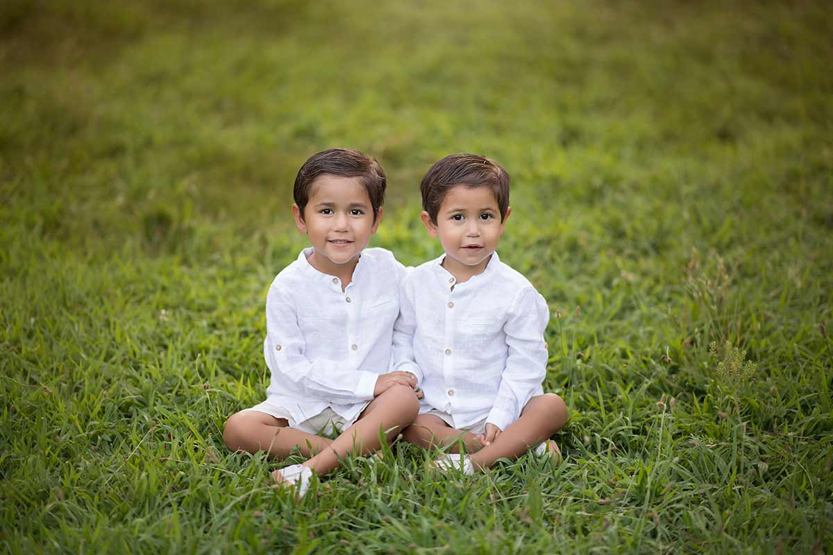 Twin boys posing for a portrait sitting in grass