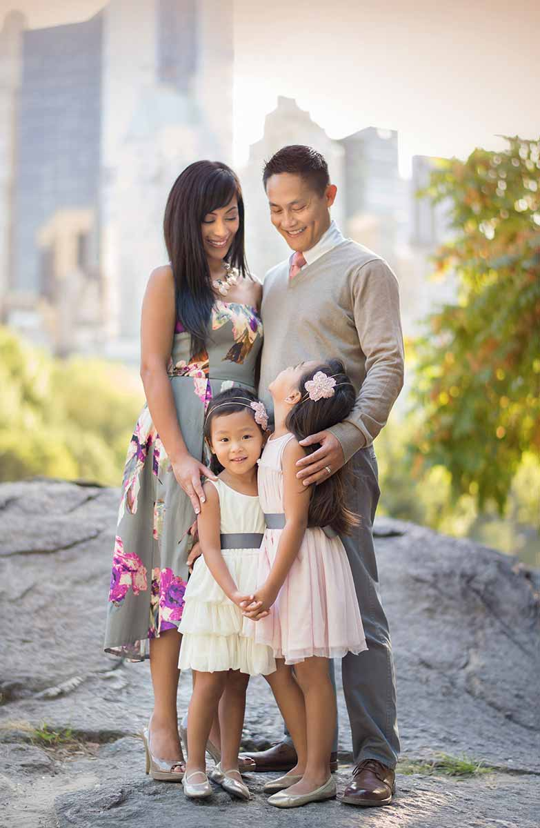 Beautiful family posing with their two daughters in Central Park