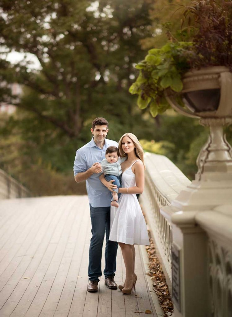 Well dressed family posing for a photo on Central Park's Bow Bridge NYC