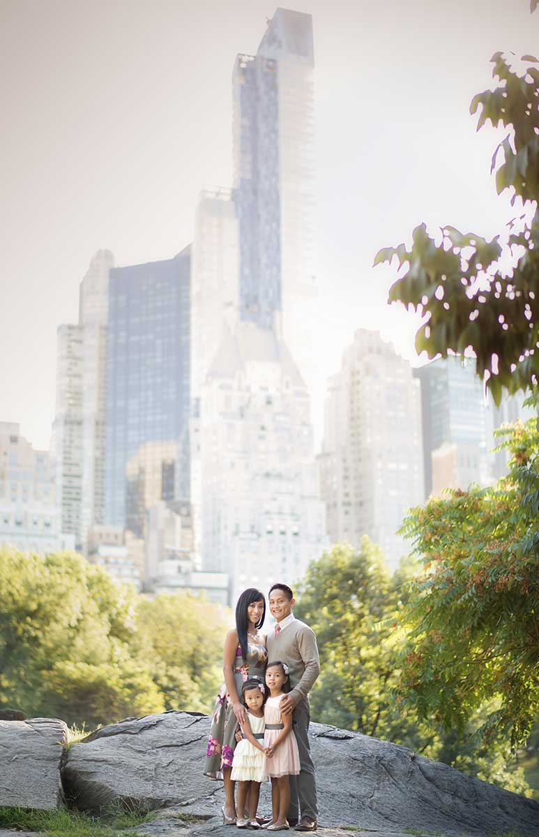 Family portrait set in NYC's Central Park with Manhattan skyline in the background