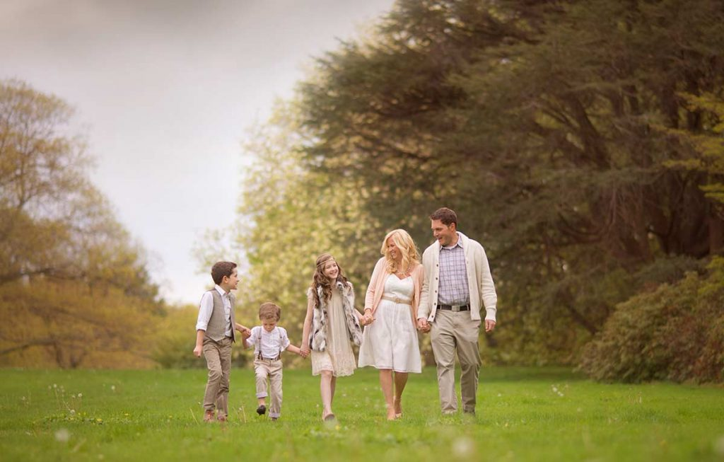 Lifestyle portrait of a beautifully styled family walking in a grass field