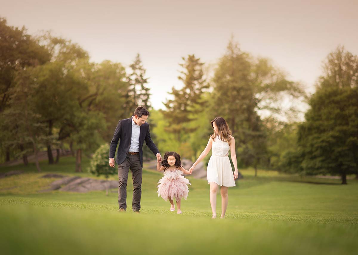 Family walking in a grass field along with their daughter in Central Park