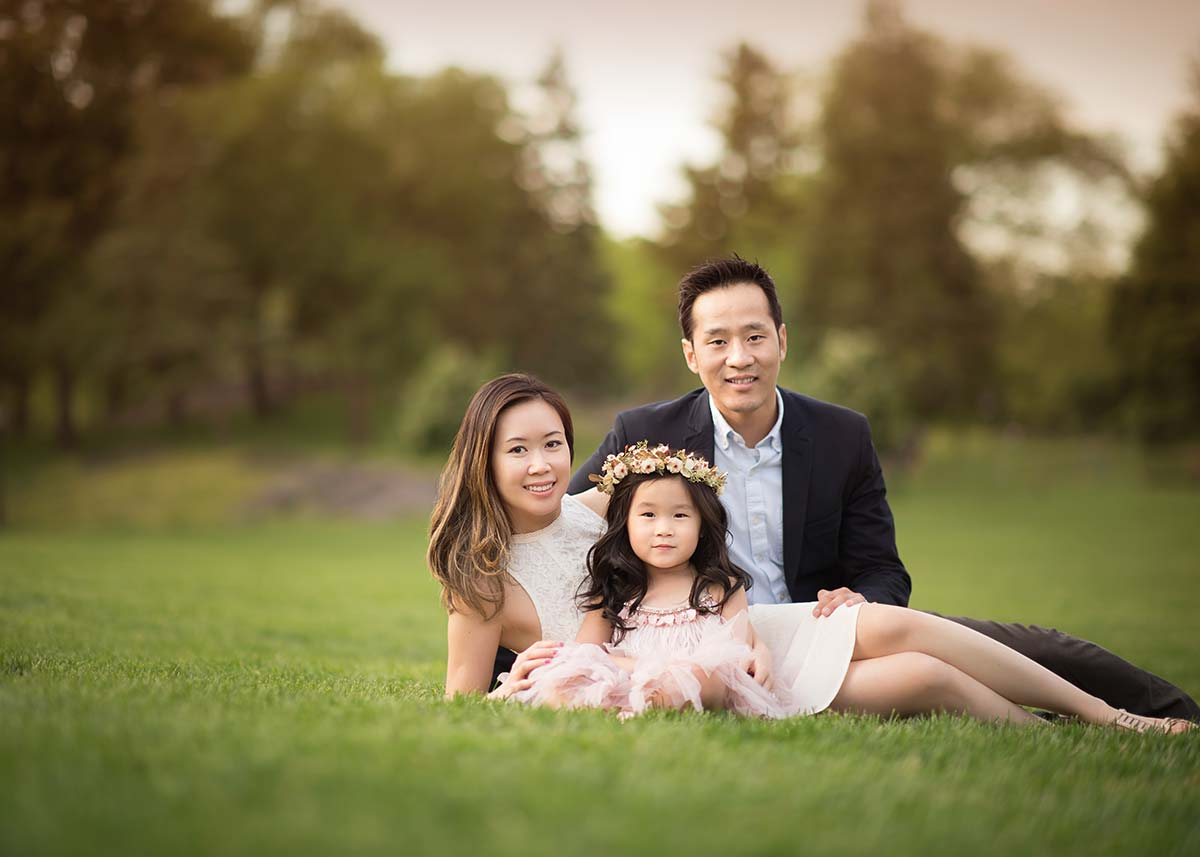 Husband and wife sitting with their daughter in a grass field