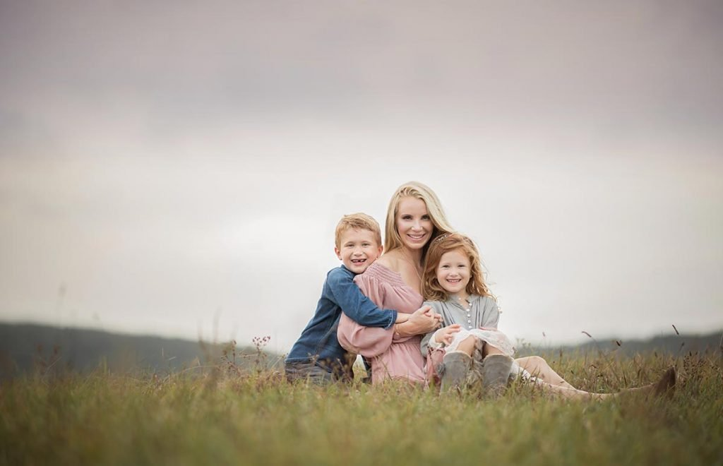 Stylish family sitting in a field of grass posing for a photo
