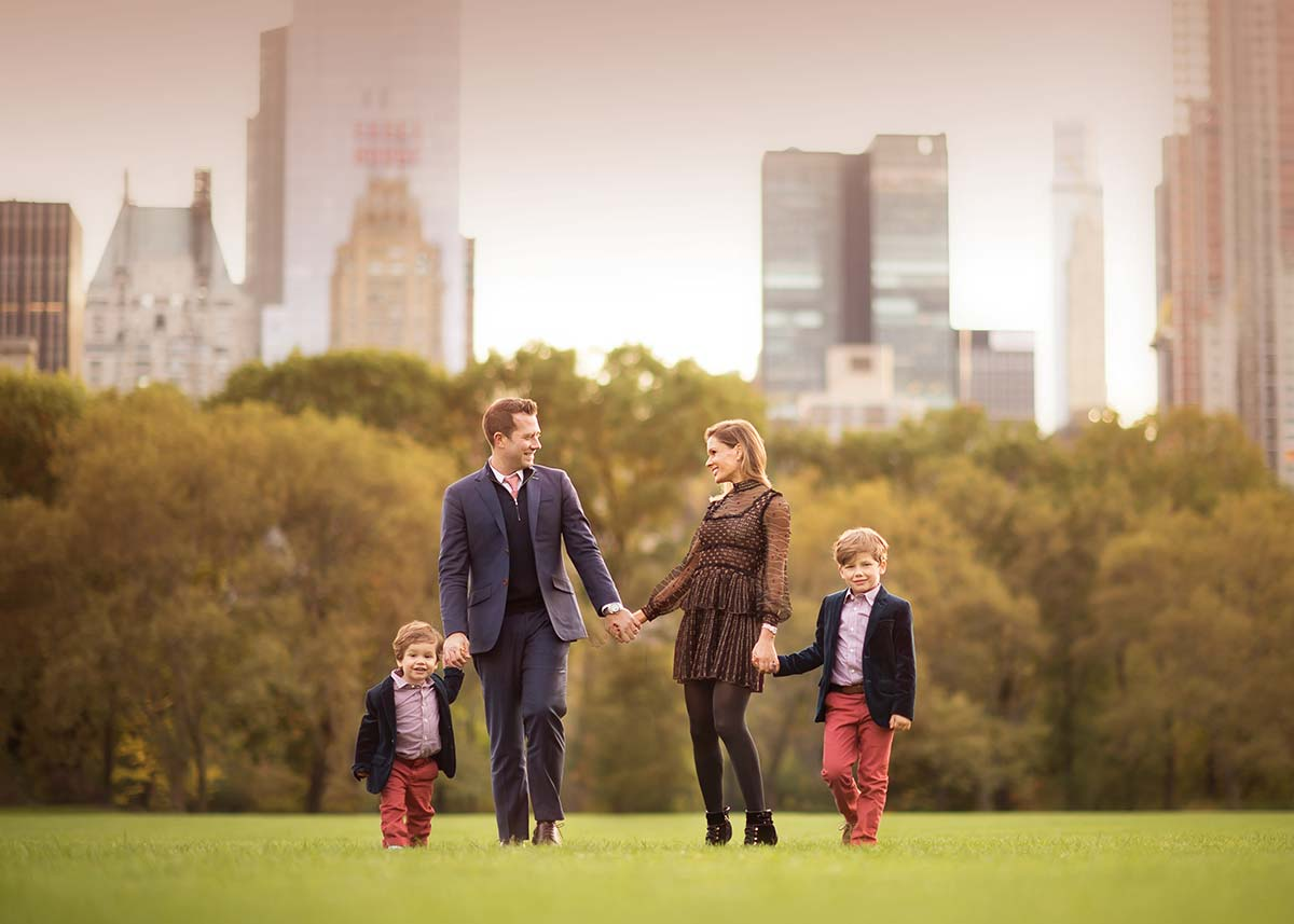 Stylish Manhattan Family walking in Central Park's Sheep Meadow and sharing a happy moment