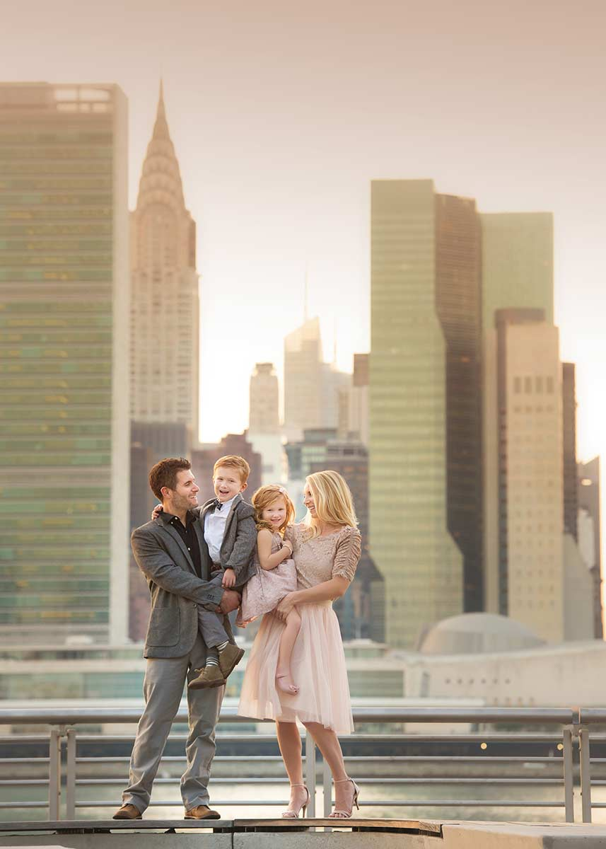 Family portrait full of smiles taken by the East River in NYC