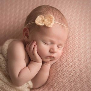 Sleeping newborn with hands on cheeks