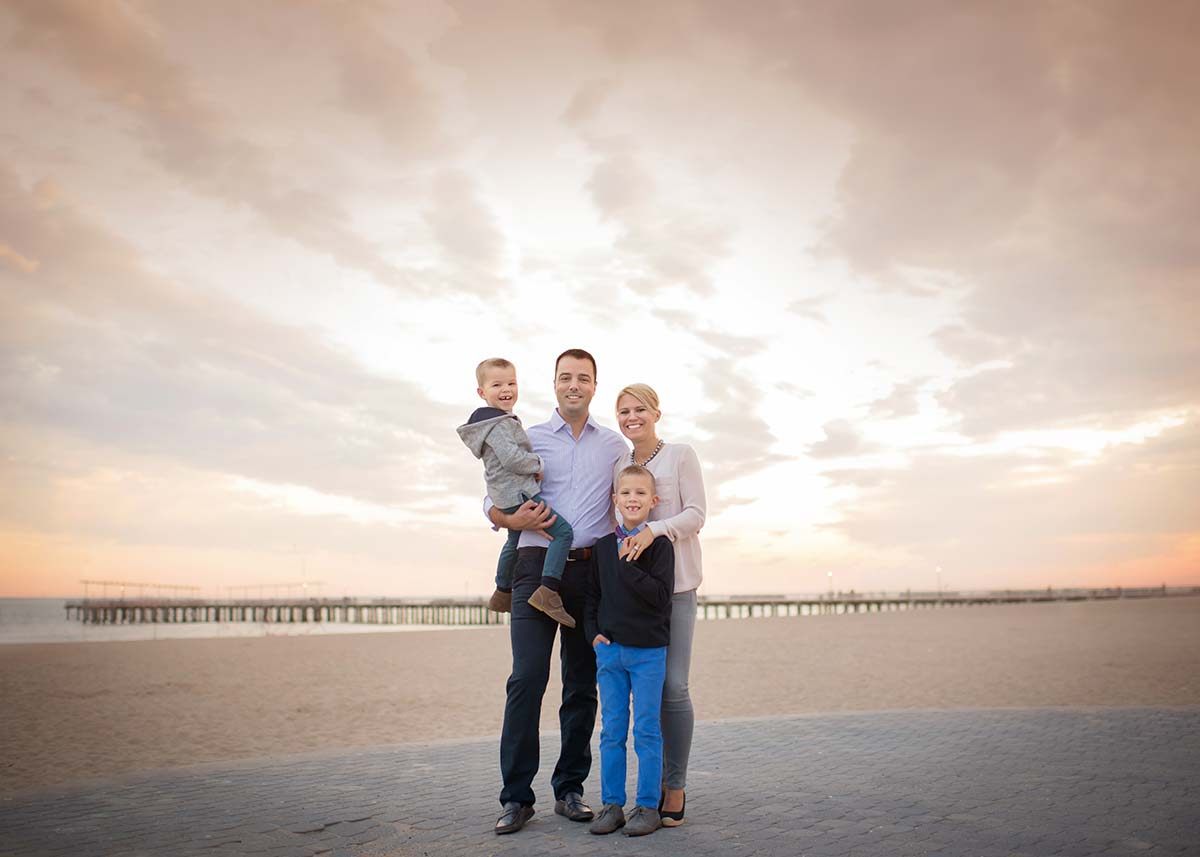 Family with two boys standing on the beach during sunset