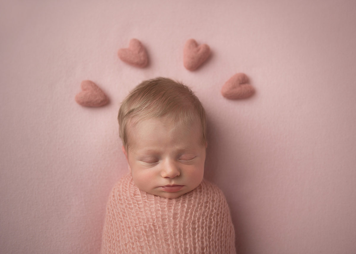 Beautiful infant sleeping with stuffed hearts