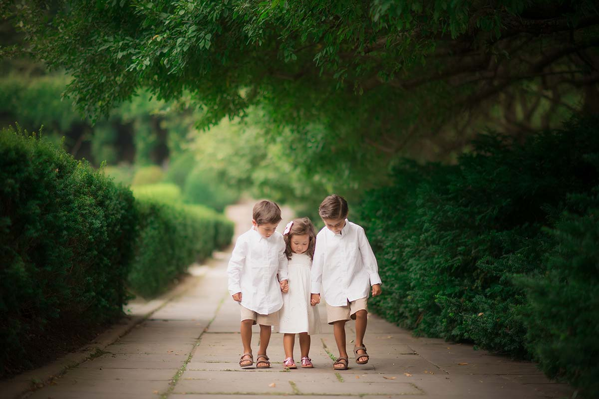 Three siblings walking through a garden