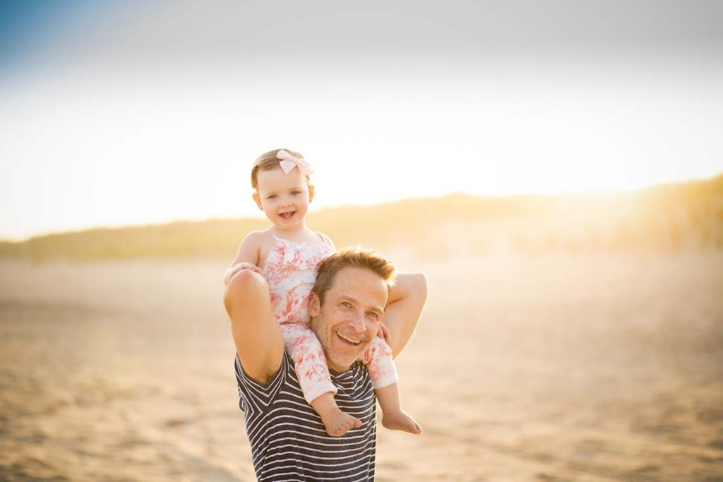 Father holding his daughter on his shoulders at the beach