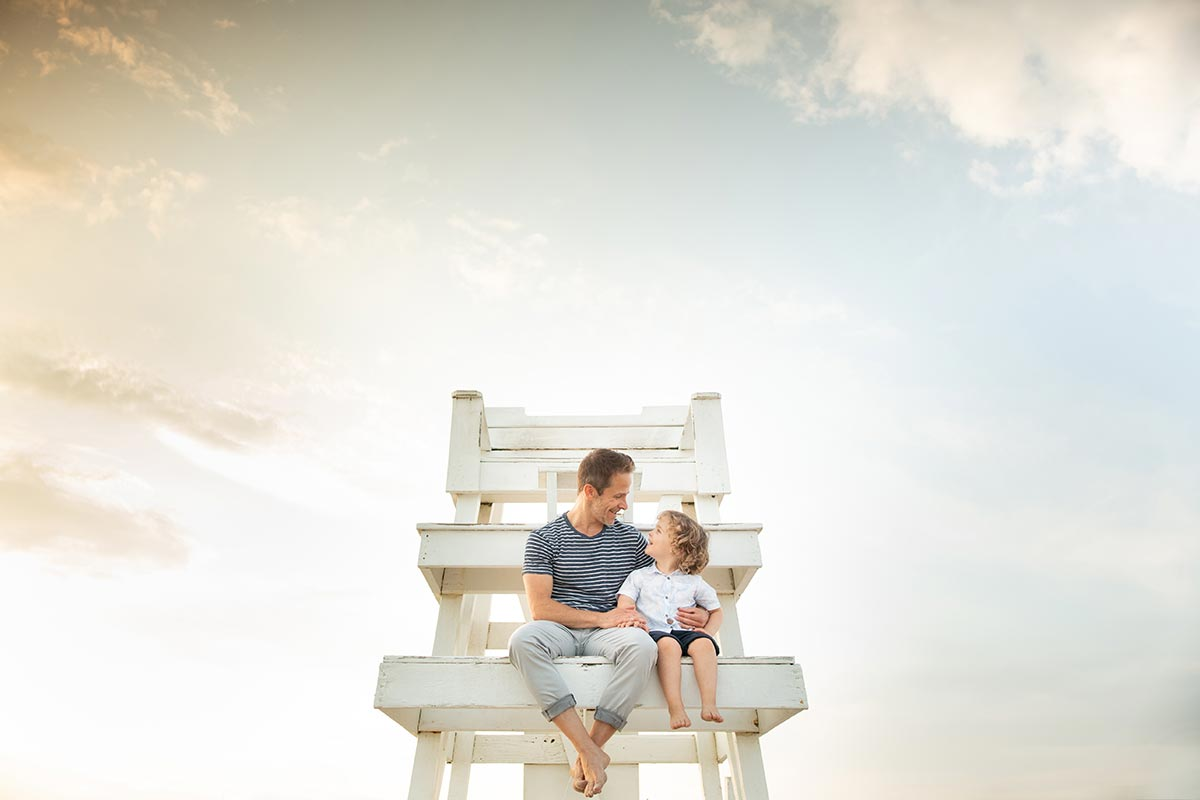 Father sitting on a lifeguard tower with his son
