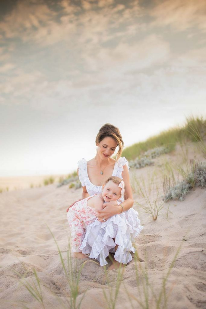 Woman in a dress playing with her daughter in the Hamptons