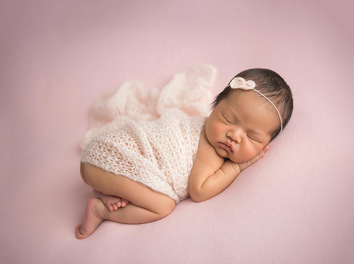 Sleeping baby with a swaddle and headband