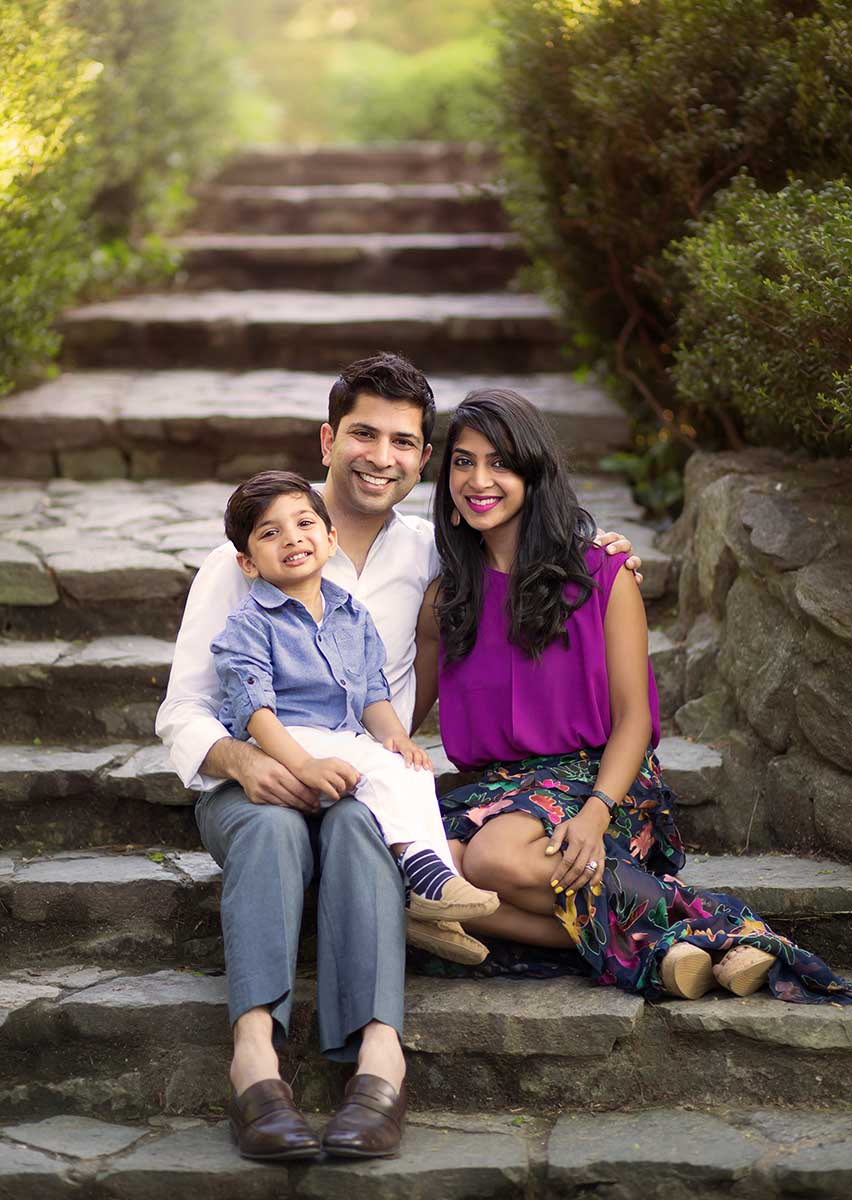 Parents and their son sitting on beautiful stone stairs