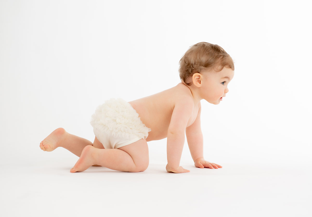 Toddler in a diaper crawling on the floor seamless white