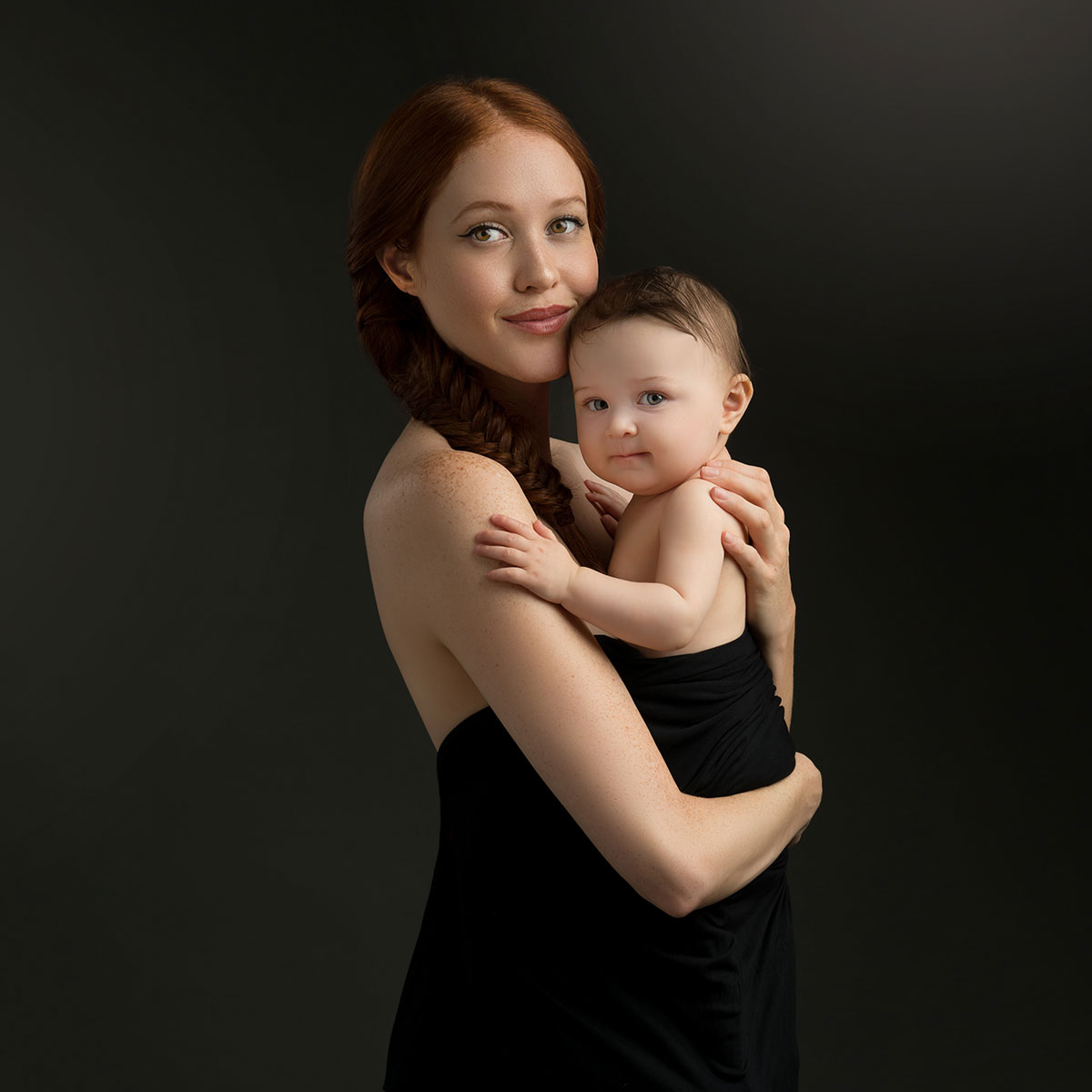 Mother in black holding her beautiful baby in a photo studio