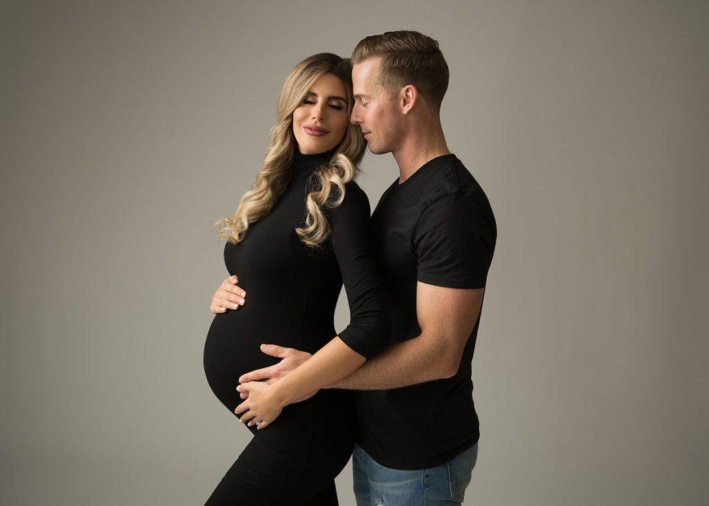 Husband and wife posing for a pregnancy photo