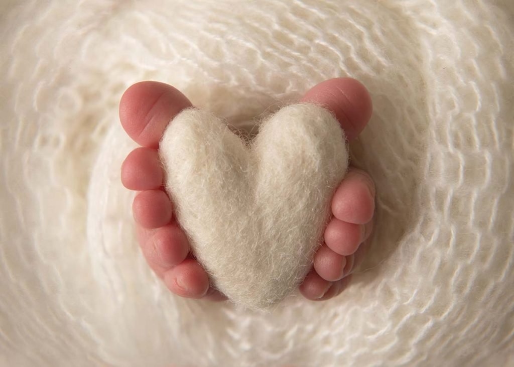 Baby toes holding a stuffed heart