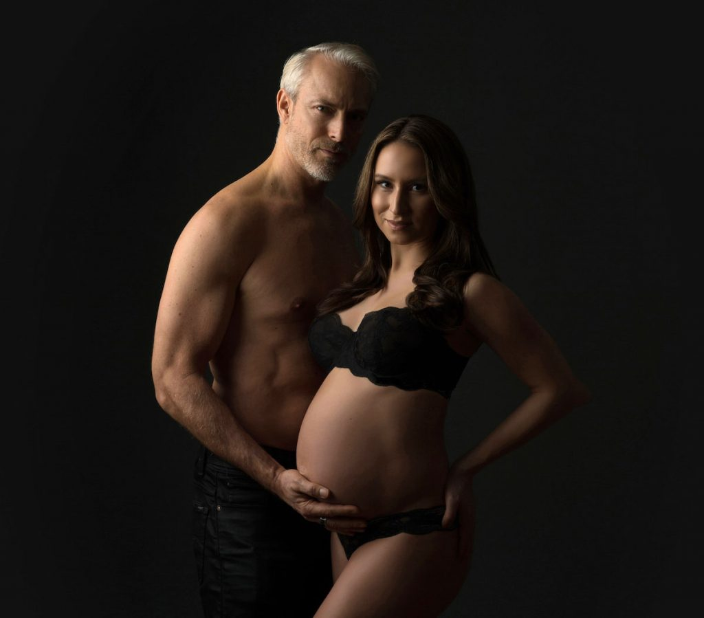 Married couple holding hands in a pregnancy pose