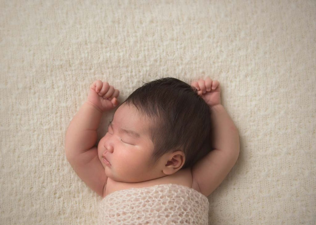 Infant sleeping peacefully with hands up