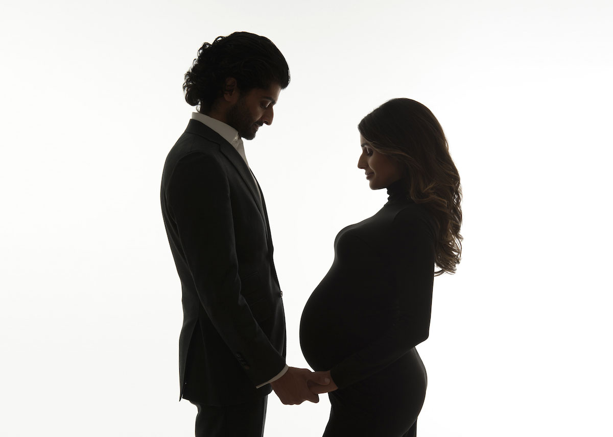 Beautiful photo of a couple holding hands with a pregnant woman