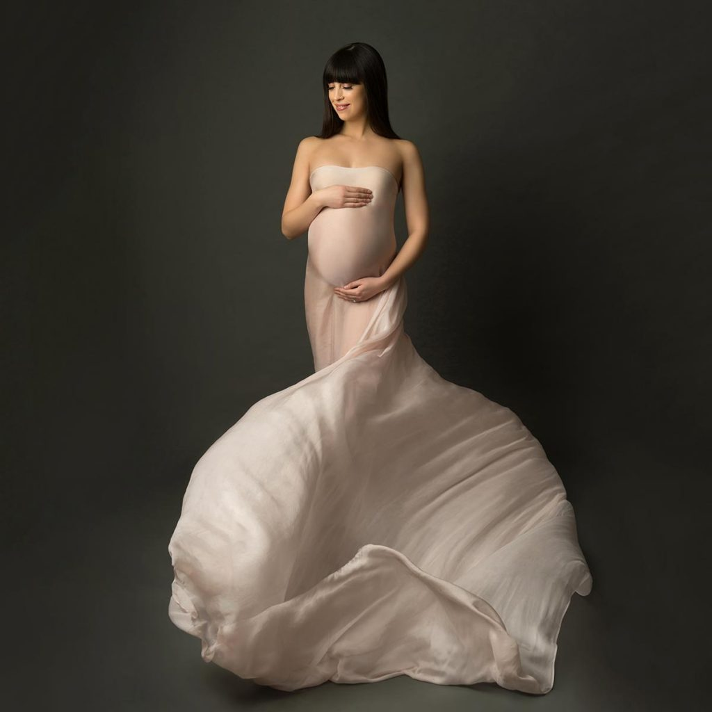 Flying silks surround this pregnant woman posing for a maternity photo