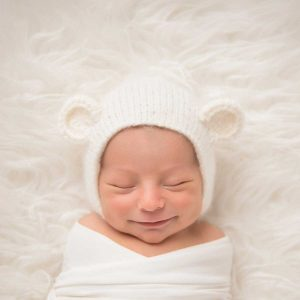 Newborn baby swaddled and smiling
