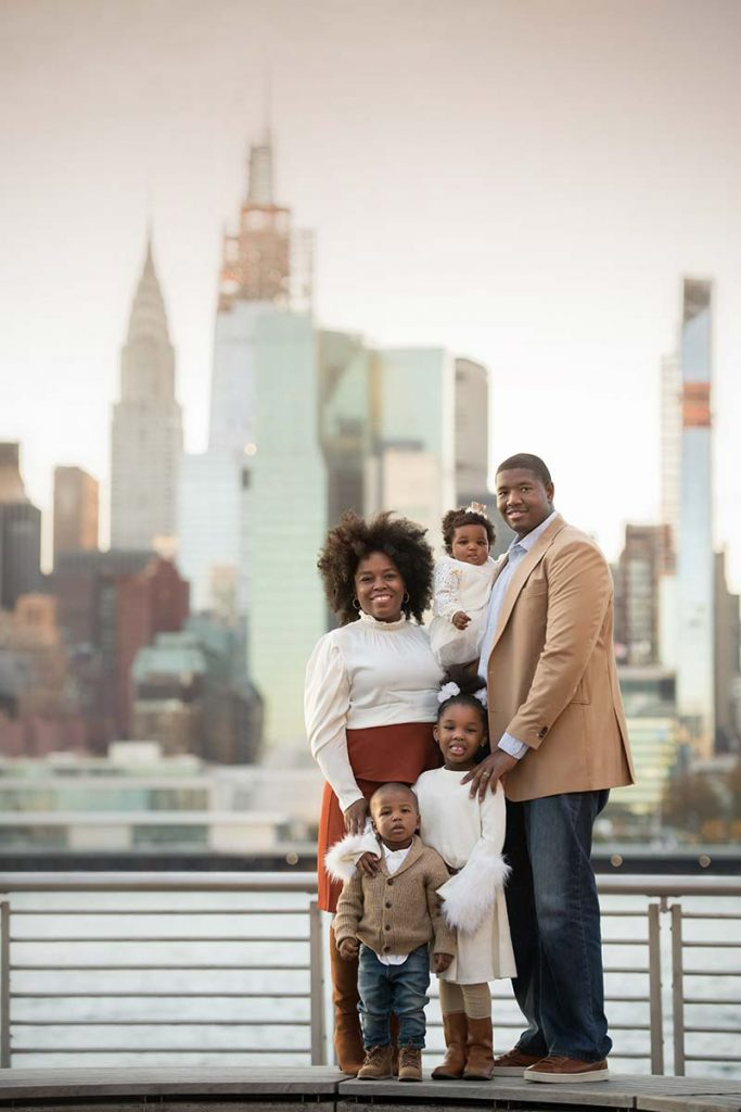 Stylish family posing for a portrait with NYC skyline
