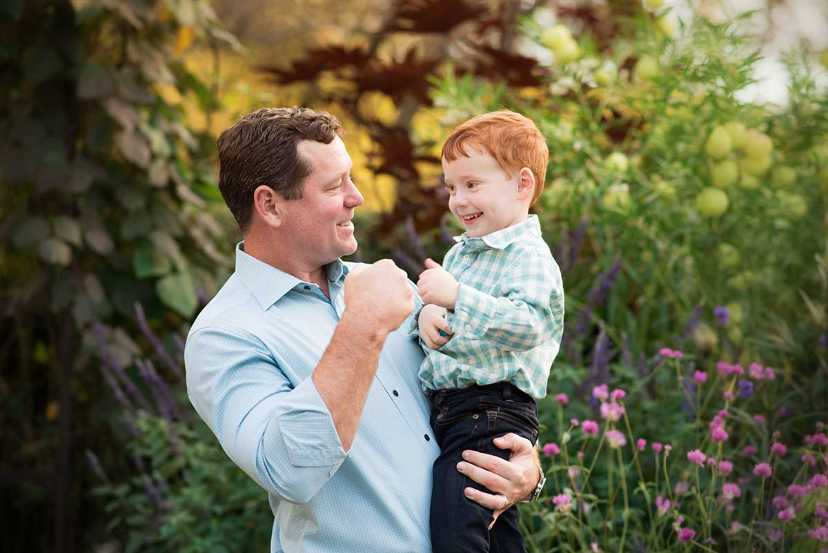 A father and son share a congratulatory fist at the botanical gardens in NYC
