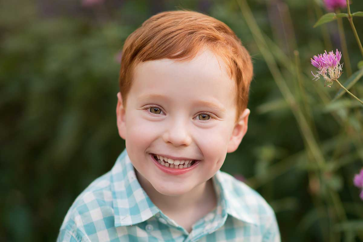 A boy with red hair smiling for the camera