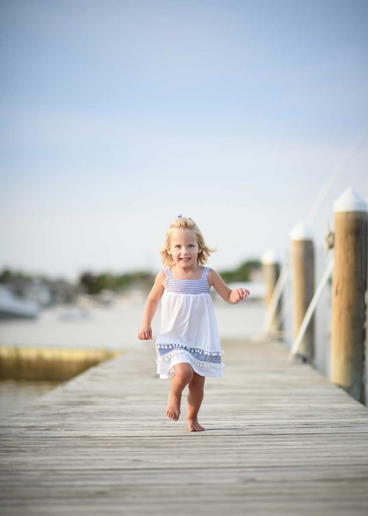 A happy girl running down a dock at a marina in the Hamptons