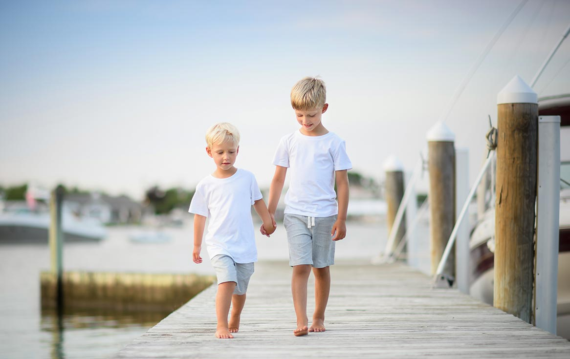 Two brothers holding hands and walking down a dock in the Hamptons