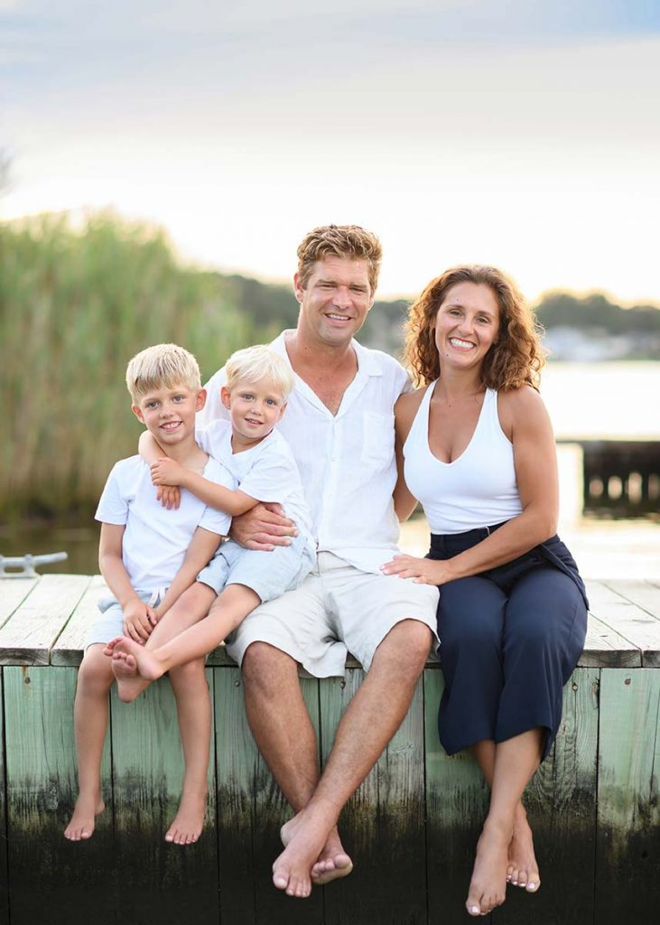 Hamptons family sitting on a dock at a marina in the Hamptons