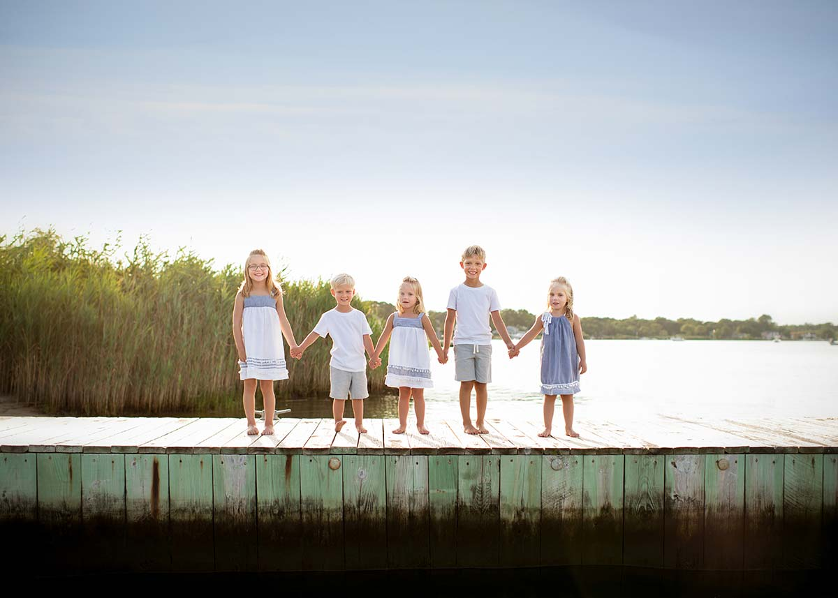 Children holding hands on a dock in the Hamptons