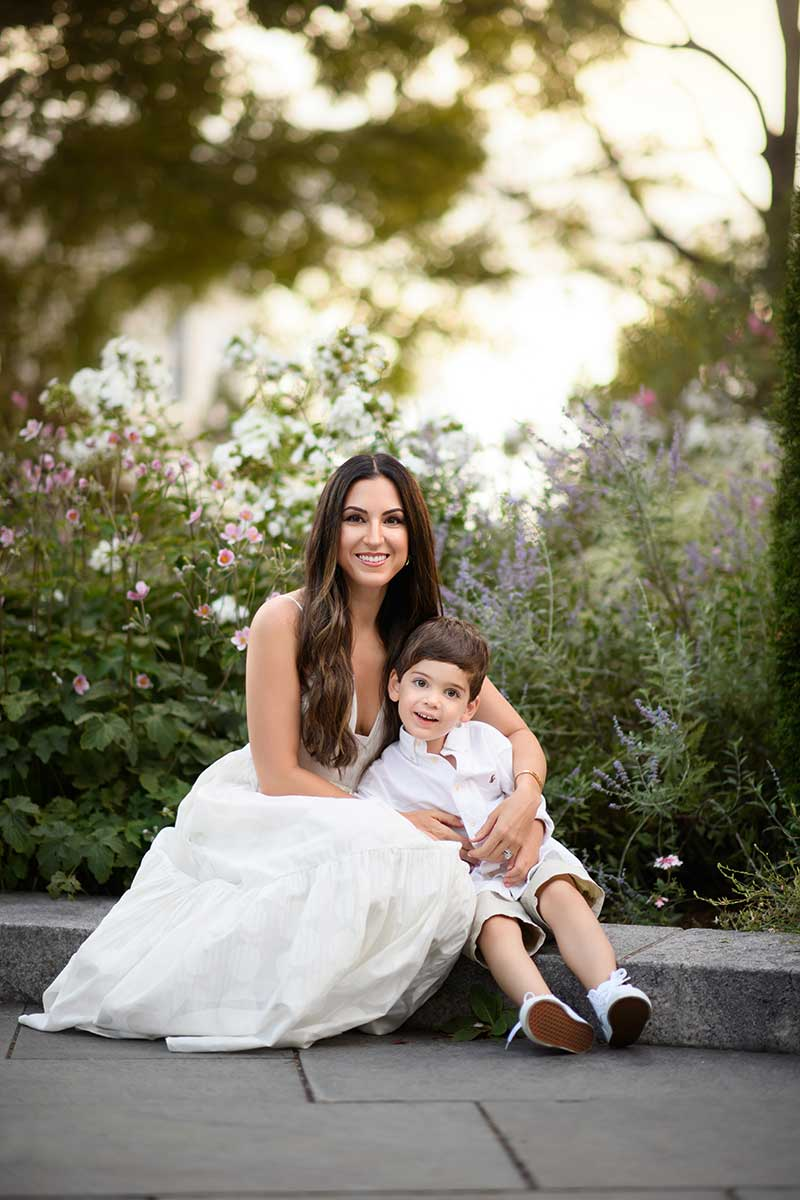 A smiling mother posing for a photo with her little son at a NYC park