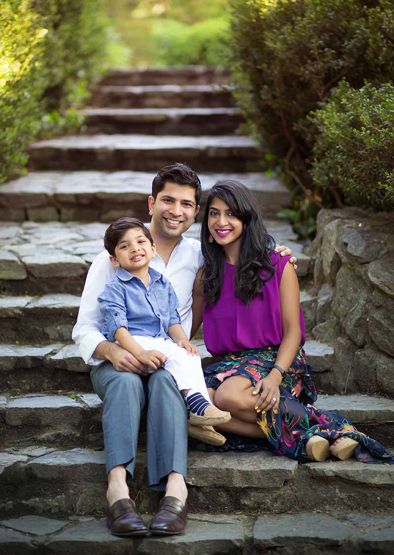 Parents share a smile with their little son on a stone staircase in NYC's Central Park
