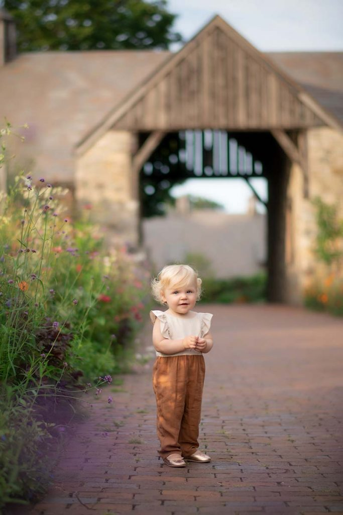 Adorable little girl standing on a brick path at a farm in Easthampton