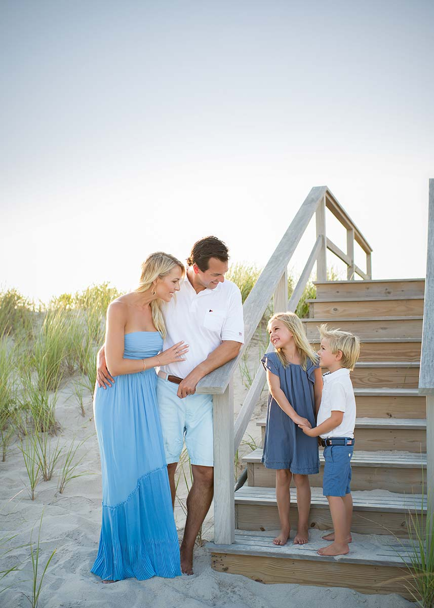 Brother and sister hold hands while sharing a smile with their Mom and Dad on a beach in the Hamptons