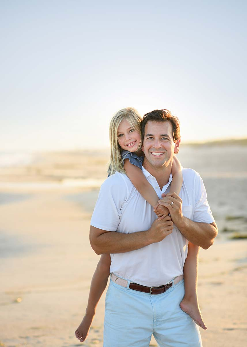 A father giving a piggyback ride to his daughter at a beach in Sag Harbor NY