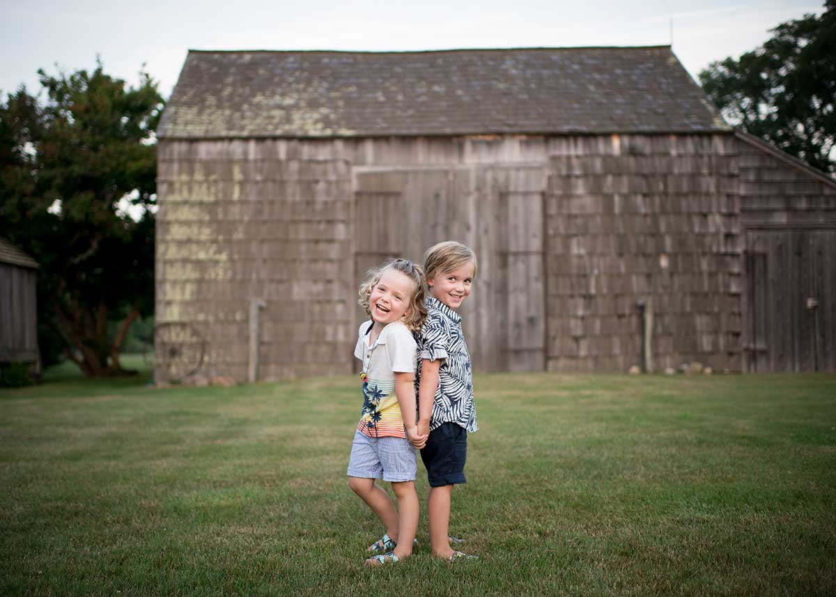 Two brothers holding hands and giggling at a rustic farm in Easthampton