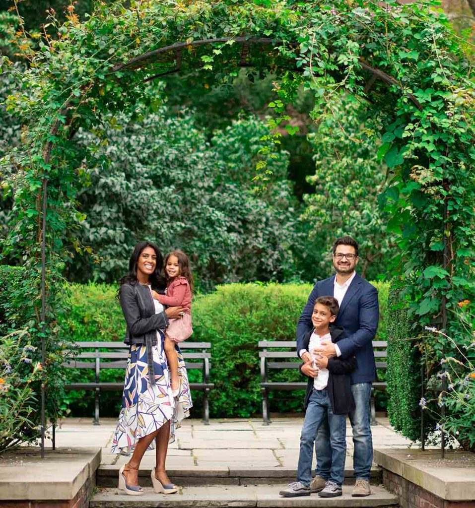 Vines growing around a steel arch frame this timeless NYC family moment